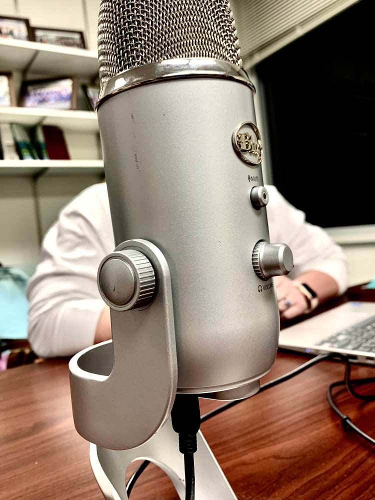 Click image to go to Episodes tab. Image: a close up photo of a gray Yeti microphone, behind which sits a person wearing a long sleeved white shirt. The angle makes it appear as though the mic has arms.