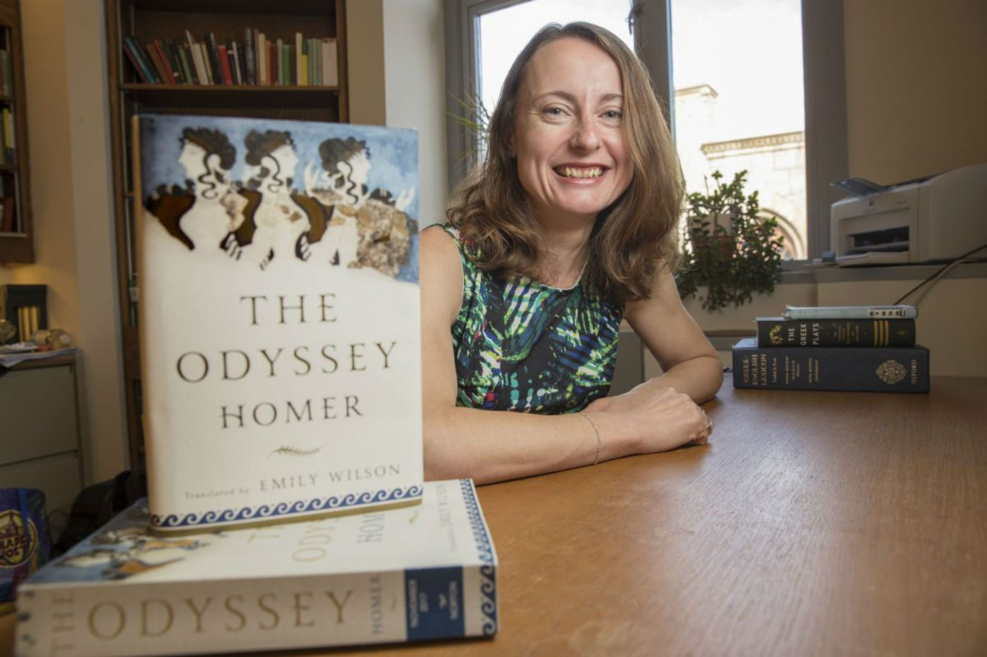 A middle-aged smiling white woman with shoulder-length auburn hair, wearing a colorful sleeveless shirt. In the foreground, her translation of the book The Odyssey by Homer is displayed.
