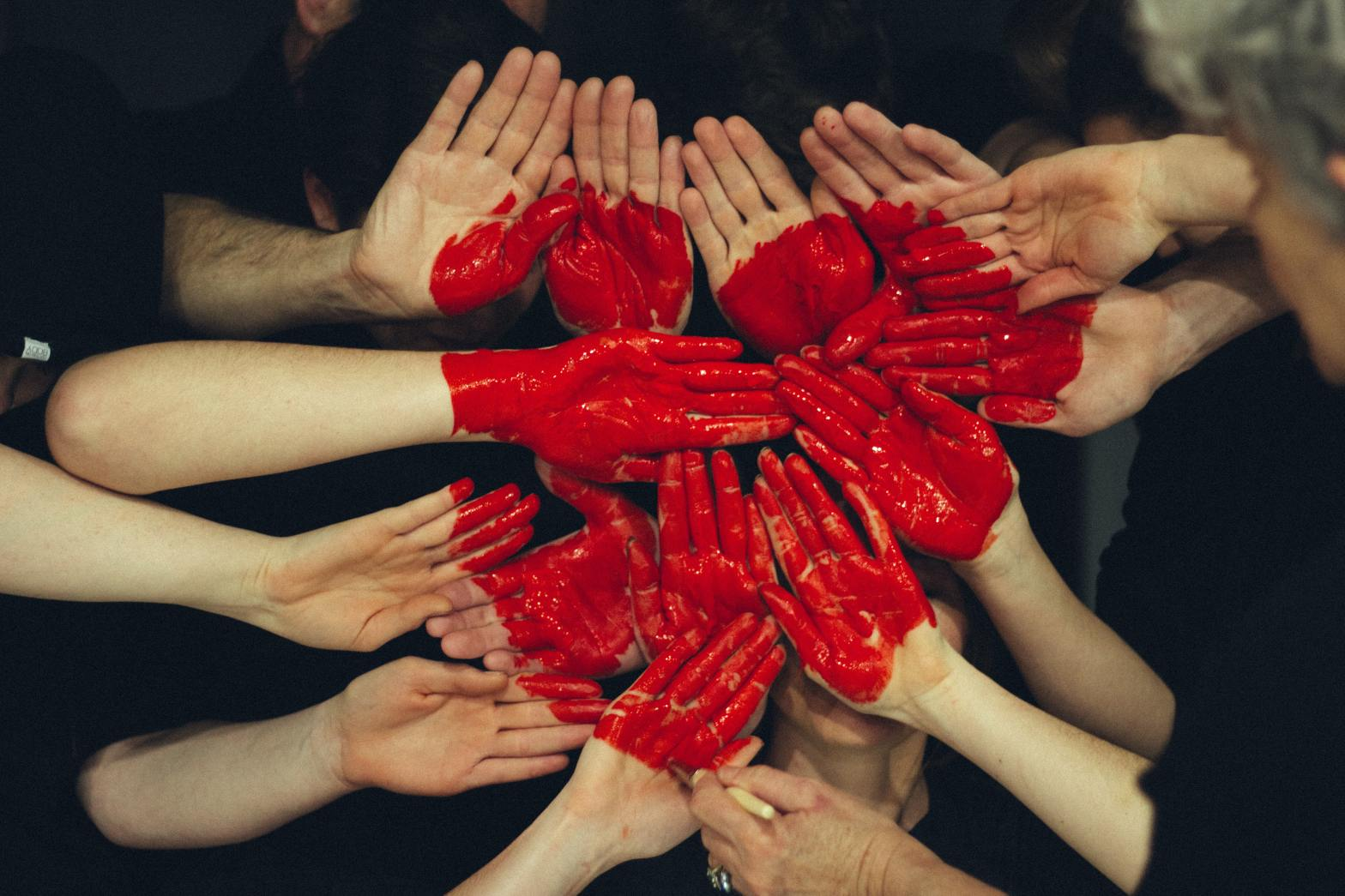 A group of people place their hands together, all palms facing outward, as another hand with a paintbrush paints a red heart shape over their hovering hands.