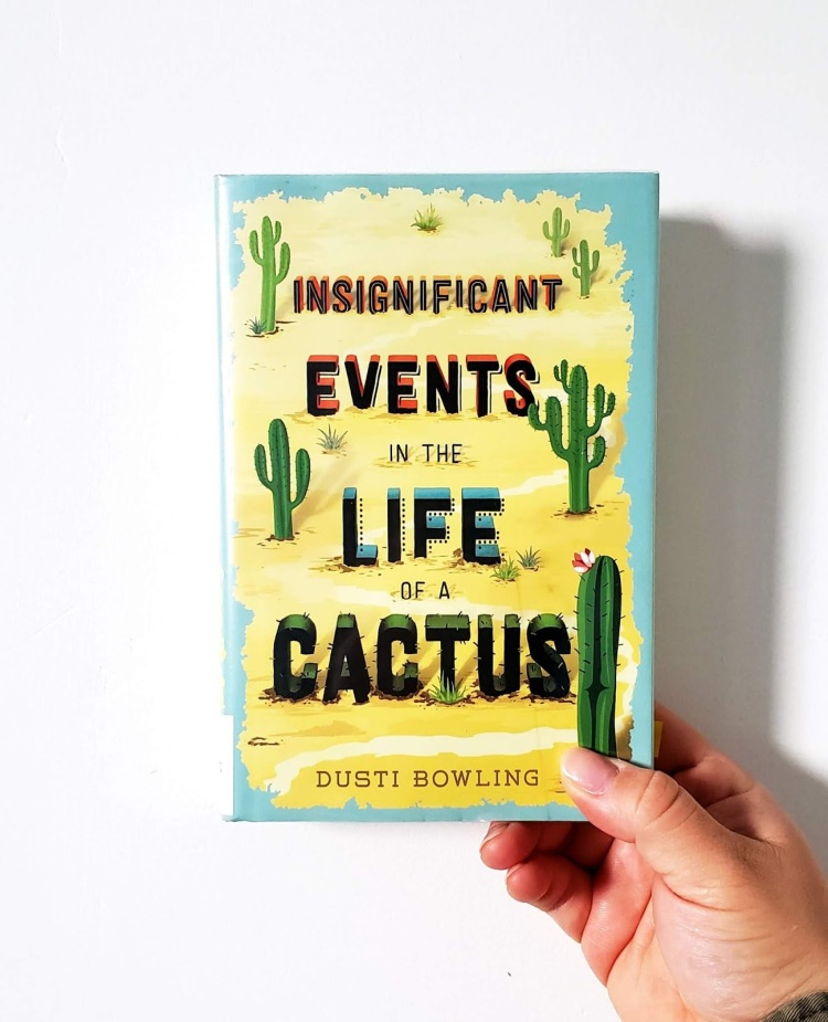 A hand holding a book up against a white wall. Book cover shows yellow sand bordered in light blue. To the left and right sides grow green saguaro cacti of different shapes and sizes. Title: Insignificant Events in the Life of a Cactus. Author: Dusti Bowling.