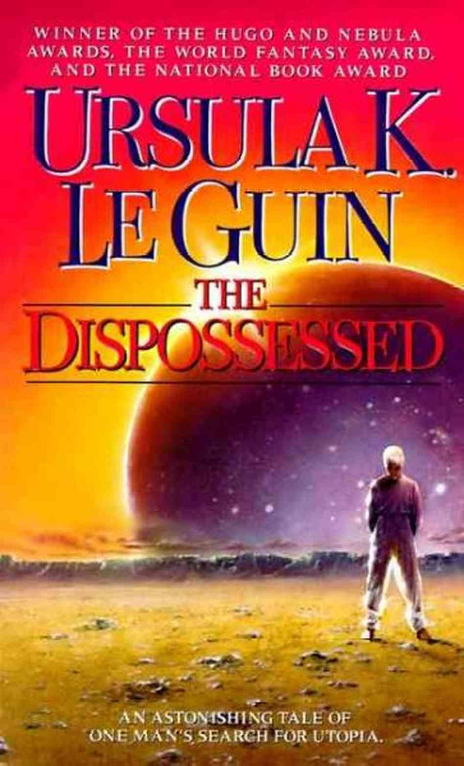 """Book cover for """"The Dispossessed"""" by Ursula K. Le Guin. The image shows a lone figure (right) standing on a barren stretch of land, looking towards a rising or setting planet in the background, which has a glint of light peeking around its edge, presumably the sun behind it. At the top, text reads, """"Winner of the Hugo and Nebula Awards, The World Fantasy Award, and the National Book Award."""" At the bottom of the cover white text reads, """"An astonishing tale of one man's search for utopia."""""""