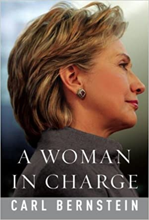 """Book cover depicting a right-facing profile portrait of Hillary Rodham Clinton. Her blond hair is cut short and brushed back from her face as she looks sternly ahead, and is wearing a gray blazer and earrings. White text along the bottom shows the title and author: """"A Woman in Charge"""" by Carl Bernstein."""