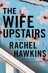 "Cover of ""The Wife Upstairs: A Novel"" by Rachel Hawkins. New York Times Bestselling author. Background depicts a blue wallpaper with white flowers. A white stair banister diagonally bisects the lower left corner. The text is large and black."